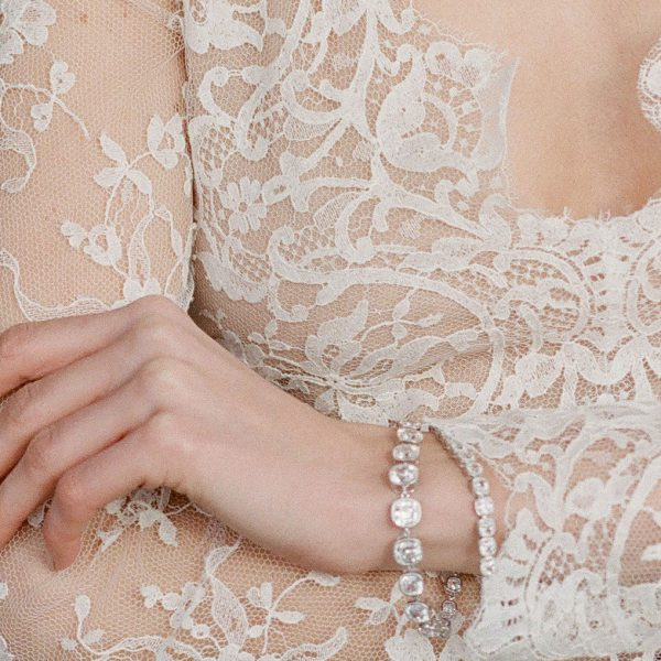 The Lucille Graduated Cushion Cut Bracelet is a sterling silver and CZ bracelet from our Signature Jewelry and Evening Jewelry Collections seen here on model.